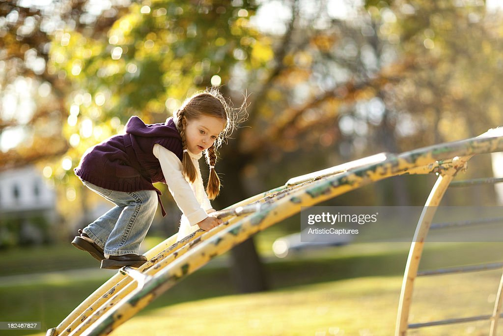Backlit Little Girl Playing in the Park on Autumn Day