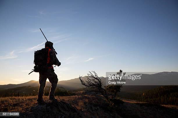 A backlit male hunter at sunrise.