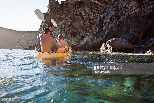 A back-lit man and a woman kayak into a rocky cove on the island of St. John, USVI.