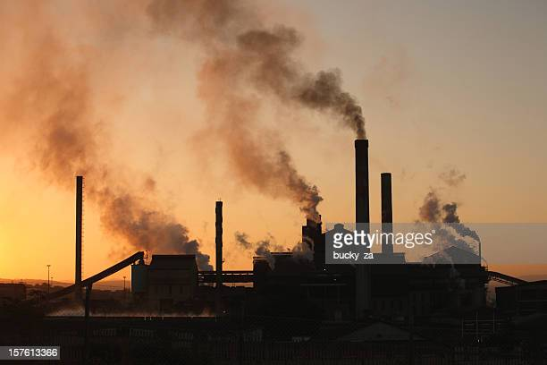 Backlit paper mill factory sunset with dark smoke rising upwards