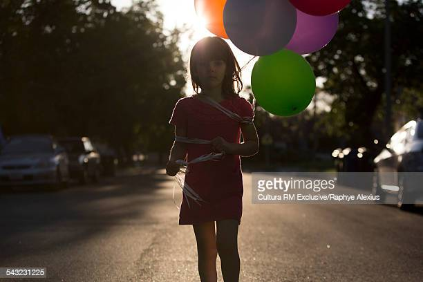 Backlit silhouetted portrait of four year old girl on street with bunch of balloons