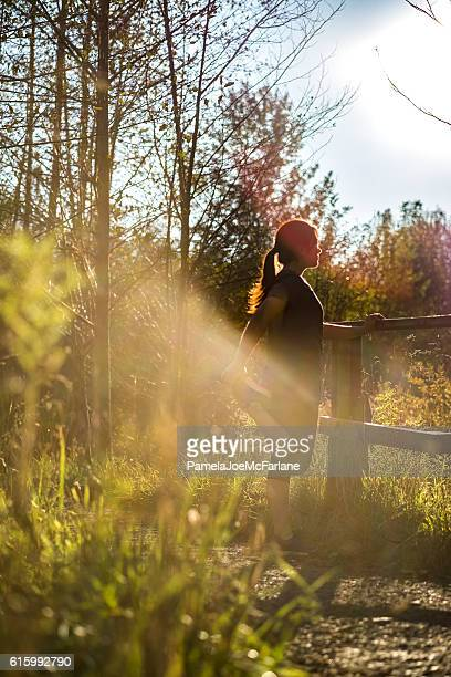 Backlit Young Woman Stretching Leg After Running on Rural Trail