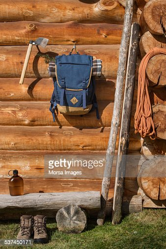 Backpack and axe hanging outside cabin