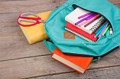 Backpack and school supplies: books, notepad, felt-tip pens, scissors on brown wooden table