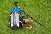 Backpack, hiking boots, water bottle and hiking pole on turf