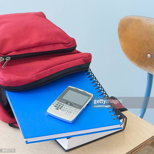 Backpack, notebooks, and PDA on school desk