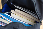 Backpack with schoolbooks and notebooks. Education concept image. Selective focus