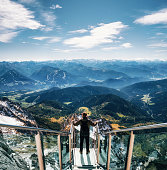 Young man with backpack stands on observation deck of skywalk rope bridge Dachstein Mountains and enjoys the landscape in Austria