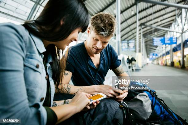 Backpacker couple checking boarding passes on their smart phone