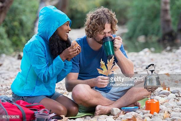 Backpacker couple having coffee break outdoor.