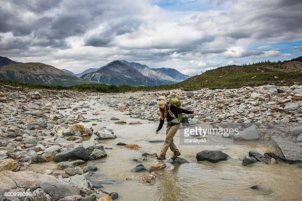 Backpacker crossing river in remote mountain wilderness, Alaska