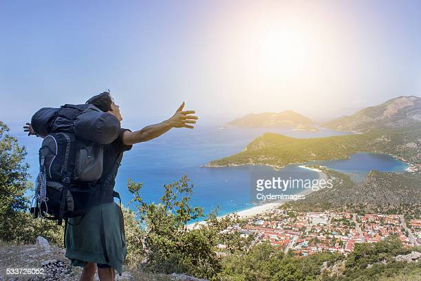 Backpacker opening his arms against Fethiye's beauty landscape