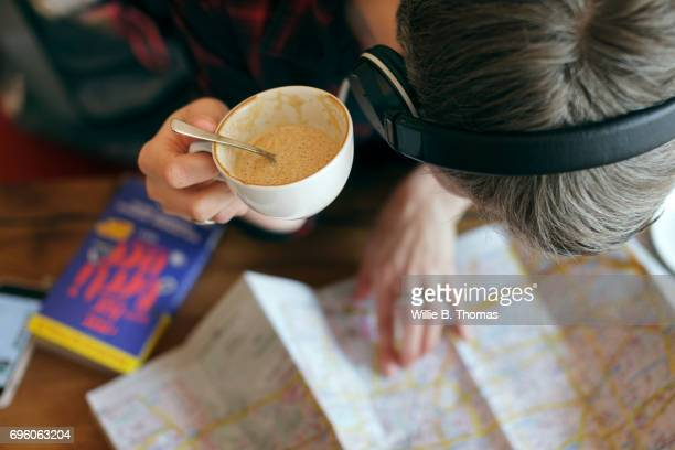 A Backpacker Reviews Her Route Whilst Sitting In A Cafe