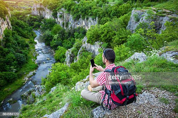 Backpacker sitting on mountain peak and typing on phone