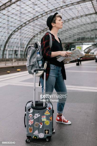 Backpacker Standing On Train Platform Looking Over Map
