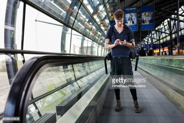 Backpacker using Mobile Phone at Airport
