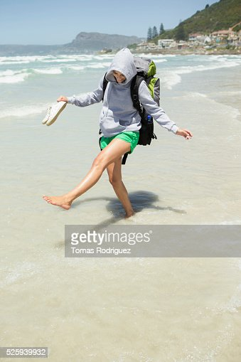 Backpacker wading in sea : Stock Photo