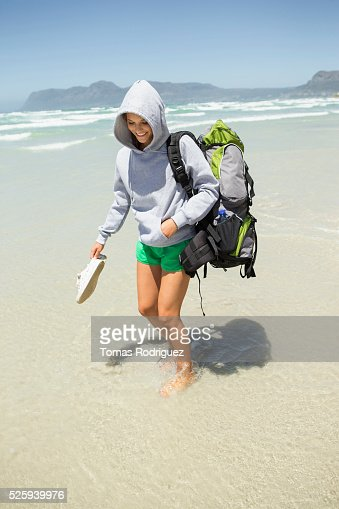 Backpacker wading in sea : Bildbanksbilder