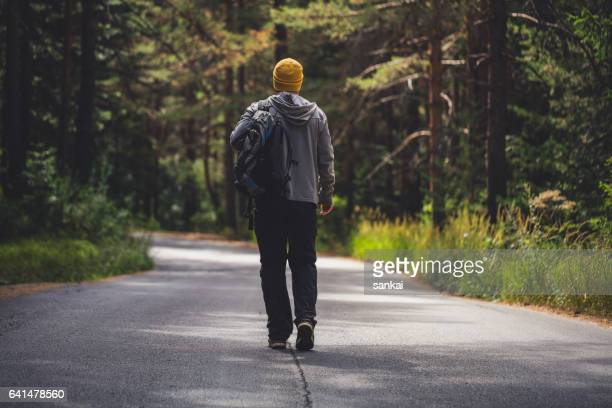 Backpacker walking alone by the road through the forest.