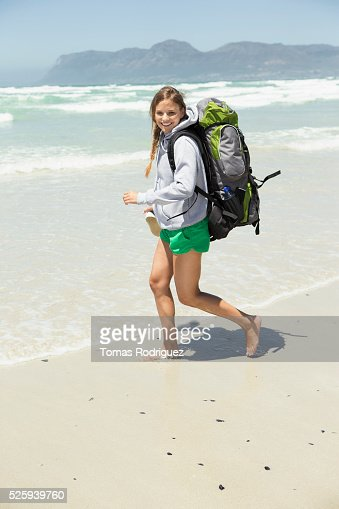 Backpacker walking on beach : Stock Photo