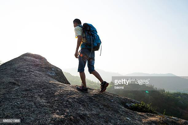 Backpacker walking on mountain peak