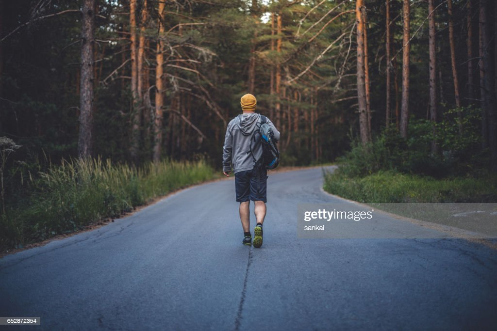 Backpacker walks alone by the road in forest : Stock Photo