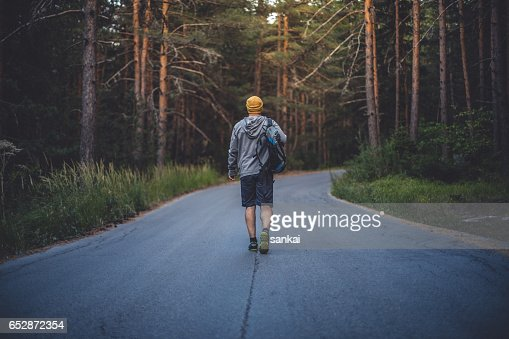 Backpacker walks alone by the road in forest : Stock-Foto