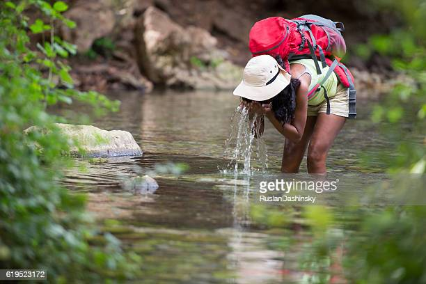 Backpacker woman refreshing her face with spring natural water.