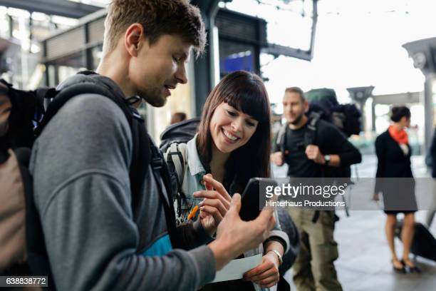 Backpackering couple using mobile boarding pass