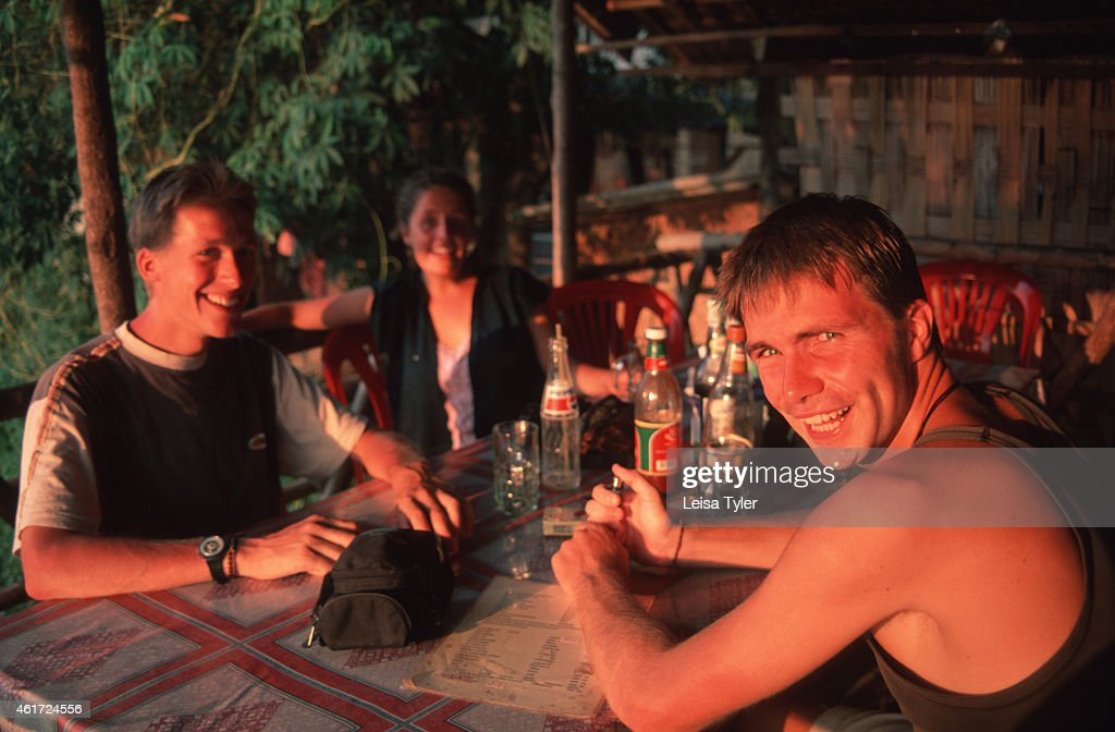 Backpackers enjoying a meal in the afternoon light at Vang Vieng Scenically spectacular Vang Vieng is home to a series of limestone outcrops with...