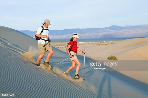 Backpackers hiking across desert sand dune
