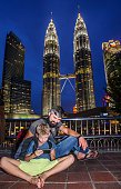 Backpackers in a big city. Father and son happy and excited together for the Malaysia trip. Holiday vacation, traveling abroad concept, copy space. Kuala Lumpur's landmark