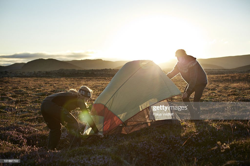2 backpackers setting up tent in the sunset : Stock Photo