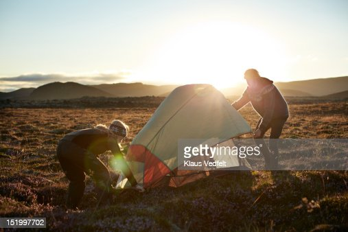 2 backpackers setting up tent in the sunset : Stockfoto