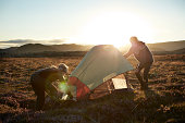 2 backpackers setting up tent in the sunset