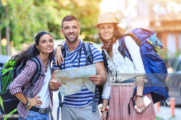 Backpackers using a map on street
