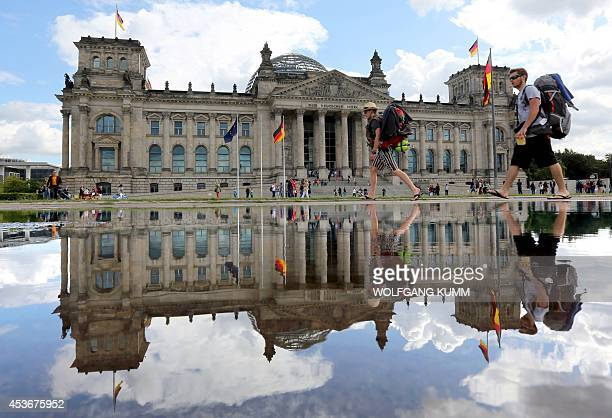 Backpackers walk past the Reichstag the building which houses the lower house of parliament as if is reflected in a rain puddle after heavy rainfall...