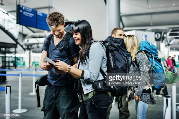 Backpackers with smart phone waiting at airline checkin counter