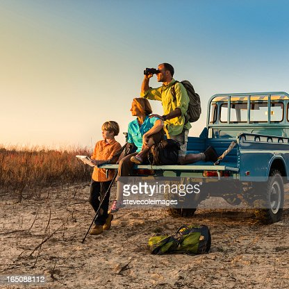 Backpacking family on vehicle at sunset