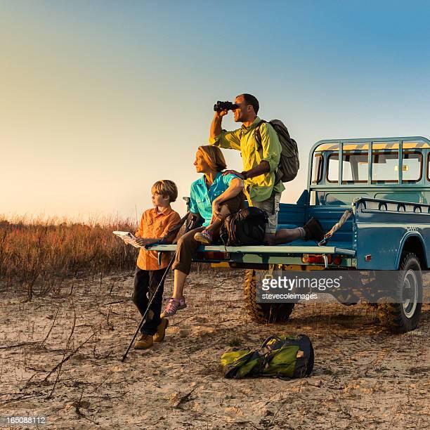 Viajar como mochilero familia en vehículo en puesta de sol