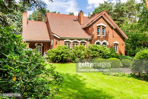 Backround yard of a beautiful english style house with bushes and green lawn. Real photo : Stock Photo
