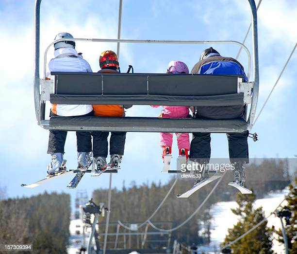 Backside view of a family on a ski vacation riding the lift