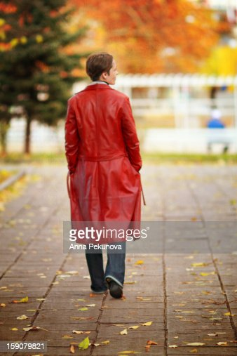 Backside view of woman in red raincoat : Stock Photo