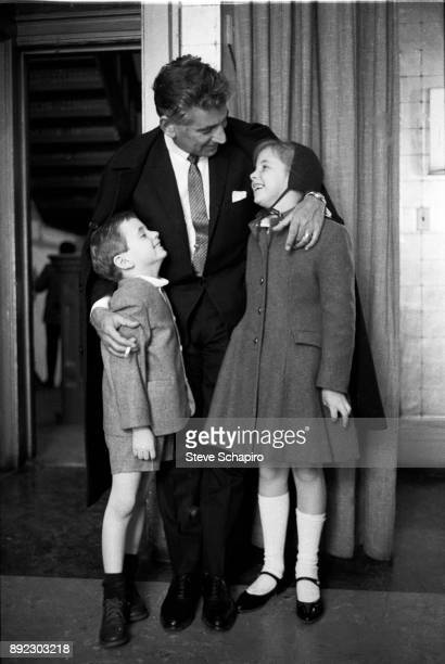 Backstage at Carnegie Hall American composer musician and conductor Leonard Bernstein smiles and embraces his children Alexander and Jamie Bernstein...