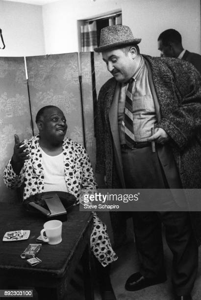 Backstage at the Apollo Theater American Jazz musician and bandleader Count Basie in a dressing gown speaks with an unidentified man New York New...
