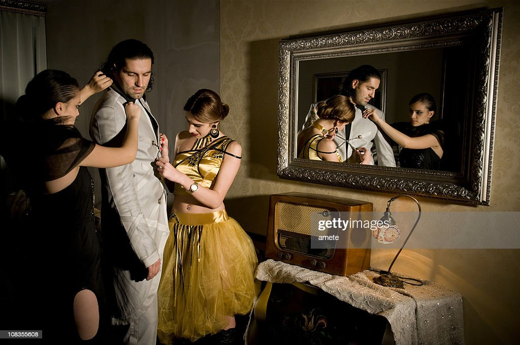 Girls helping a guy to get ready for going out : Stock Photo