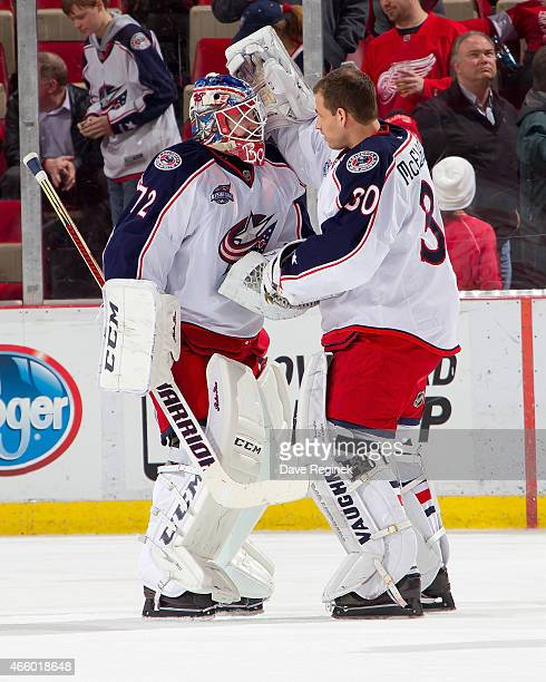 Backup goalie Curtis McElhinney of the Columbus Blue Jackets congratulate starting goalie and teammate Sergei Bobrovsky on the victory after a NHL...