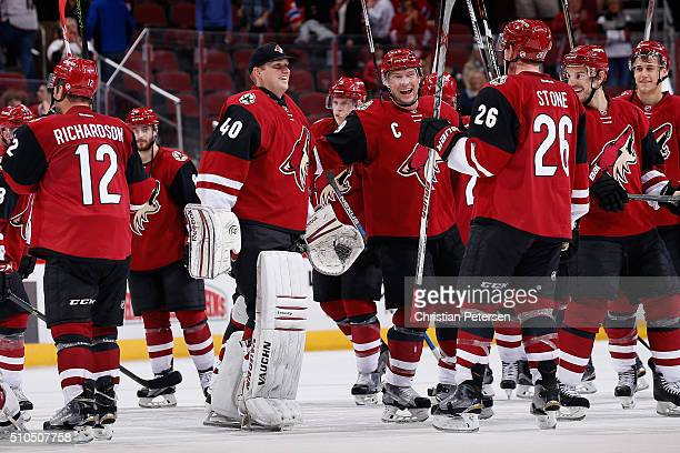 Backup goaltender Nathan Schoenfeld of the Arizona Coyotes celebrates on the ice with Shane Doan and Michael Stone following the NHL game against the...