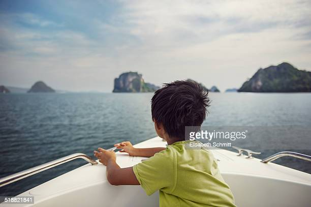 Backview of boy sitting in a moving yacht