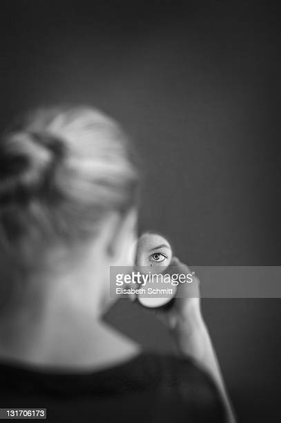 Backview of girl, watching herself in mirror